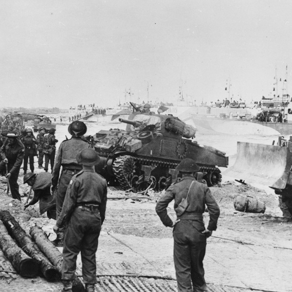 A Sherman tank of the 27th Canadian Armoured Regiment (Sherbrooke Fusiliers), supporting 9th Canadian Infantry Brigade, comes ashore on Nan White beach, Juno area, near Bernieres-sur-Mer, 6 June 1944.